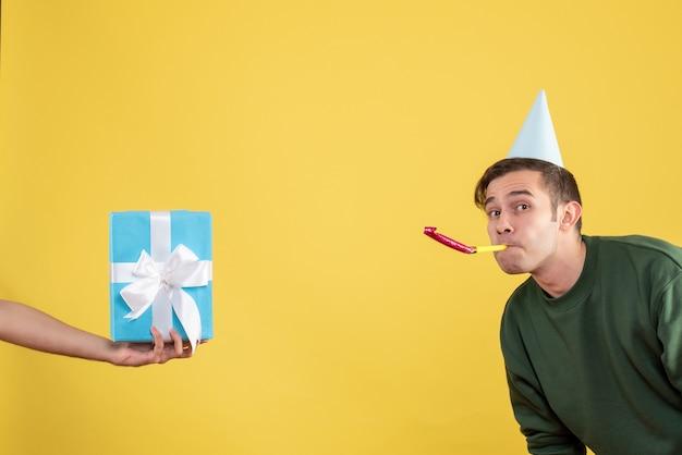 Vista frontale ha sorpreso il giovane che utilizza il regalo del noisemaker in mano umana su colore giallo Foto Gratuite