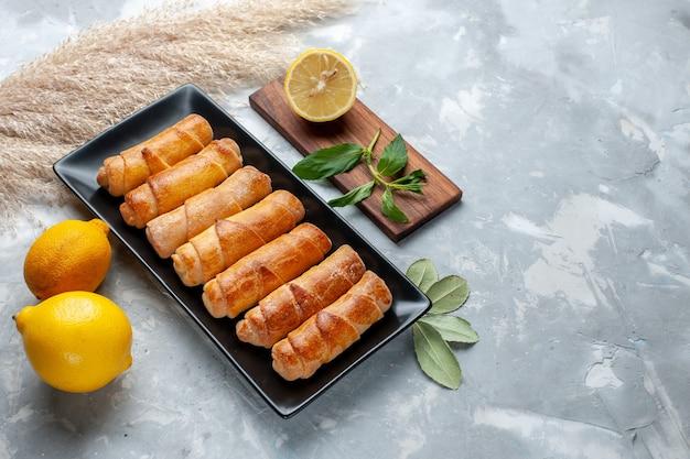 Vista frontale braccialetti dolci con limone sul tavolo luminoso, torta di pasticceria cuocere zucchero dolce Foto Gratuite