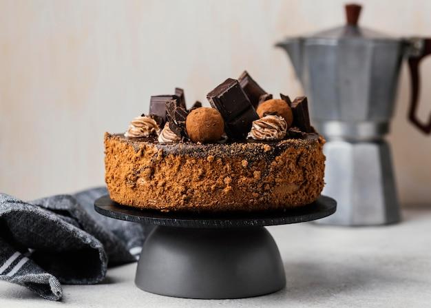 Vista frontale della torta al cioccolato dolce su supporto con bollitore Foto Gratuite