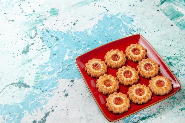 Biscotti dolci di vista frontale con marmellata di arance all'interno del piatto rosso sulla superficie blu Foto Gratuite