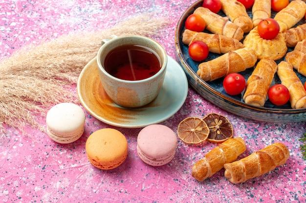 淡いピンクの机の上に新鮮なサワープラムフレンチマカロンとお茶の正面図甘いおいしいベーグル 無料写真