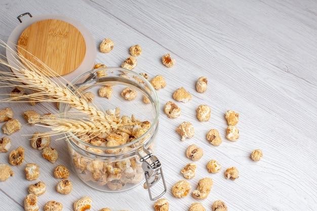 Popcorn dolce vista frontale sulla superficie bianca Foto Gratuite
