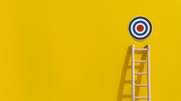 Front view of target with ladder reaching to it and copy space Premium Photo