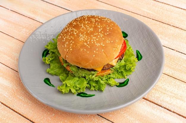 木製のクリーム色の床のハンバーガーファーストフードパンバーガーのプレートの内側にグリーンサラダと野菜を添えた正面図のおいしいチキンサンドイッチ 無料写真
