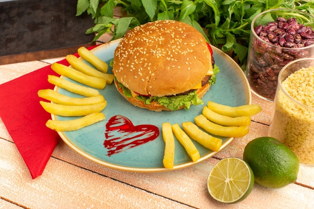 Front view tasty chicken sandwich with green salad and vegetables inside plate with french fries on the wooden cream desk. Free Photo