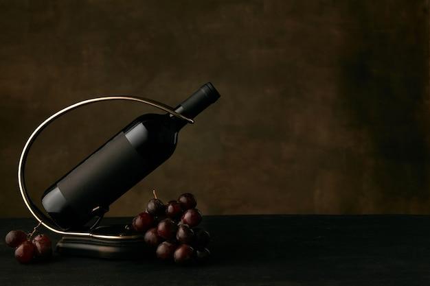 Vista frontale del piatto gustoso dell'uva dell'uva con la bottiglia di vino sul buio Foto Gratuite