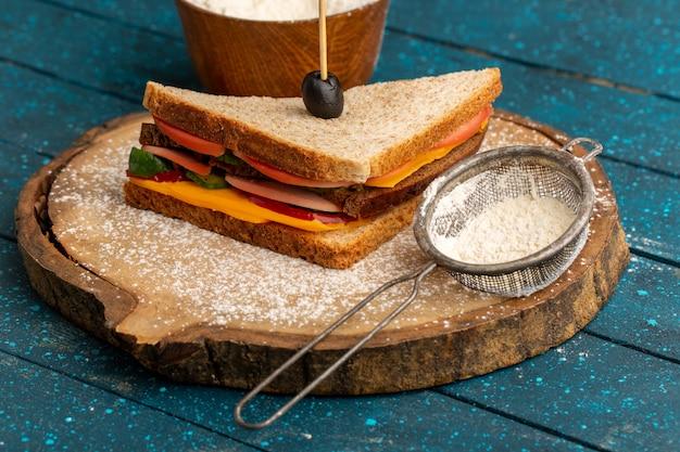 正面にチーズハムを入れたおいしいトーストサンドイッチとブルーの小麦粉 無料写真