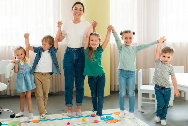 Учитель и дети, позирует вместе Бесплатные Фотографии