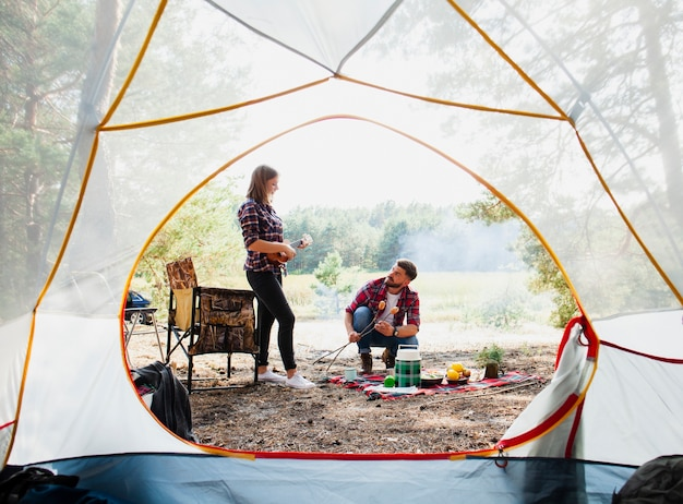 Front view tent and couple cooking Free Photo