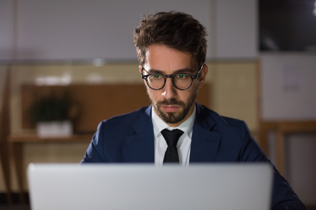 Front view of thoughtful man in eyeglasses looking at laptop Free Photo