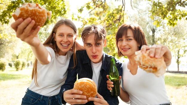 Vista frontale di tre amici al parco con hamburger e birra Foto Gratuite