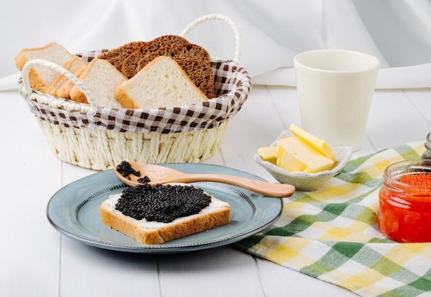 Vista frontale brindisi con caviale nero con un cucchiaio su un piatto con burro di caviale rosso e pane in un cestino Foto Gratuite