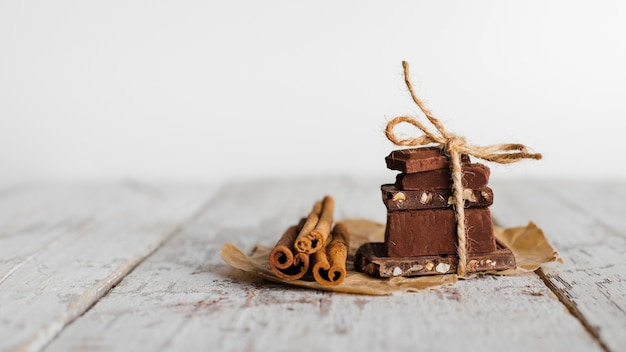 Front view tower of chocolate sweets and cinnamon sticks on paper bag Free Photo
