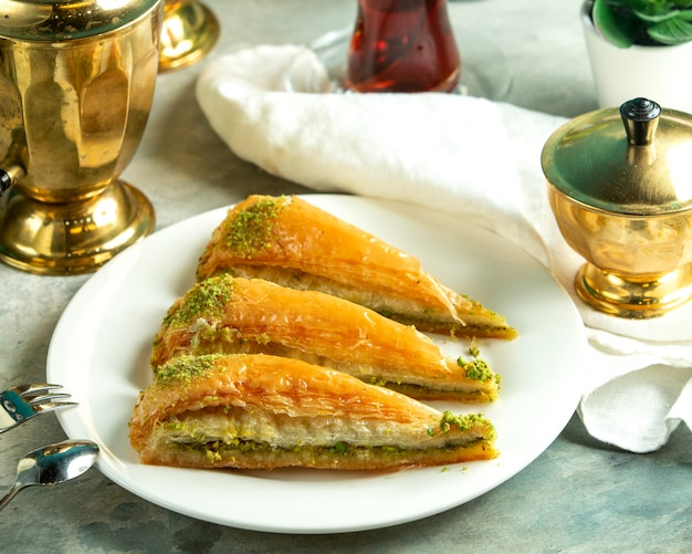 Front view traditional turkish sweetness turkish baklava with a glass of tea Free Photo