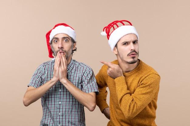 Vista frontale due ragazzi curiosi con cappelli di babbo natale uno che mette la mano sulla mascella e l'altro dito del punto che mostra il suo amico su sfondo beige isolato Foto Gratuite