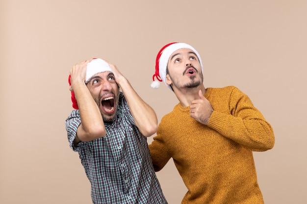 Vista frontale due ragazzi spaventati con cappelli di babbo natale guardando in alto su sfondo beige isolato Foto Gratuite