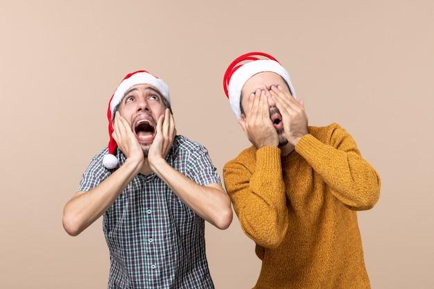Vista frontale due ragazzi spaventati con cappelli di babbo natale uno che copre le orecchie e l'altro il viso su sfondo beige isolato Foto Gratuite