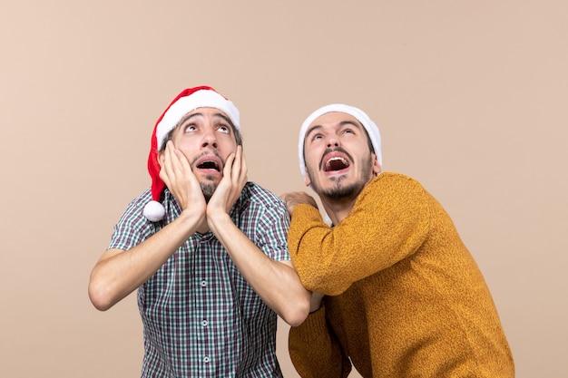 Vista frontale due ragazzi spaventati con cappelli di babbo natale uno che copre le orecchie mentre guarda in alto su sfondo beige isolato Foto Gratuite
