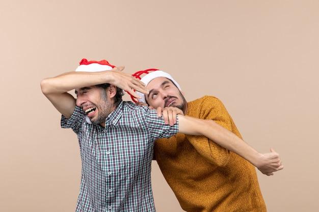 Vista frontale due ragazzi spaventati con cappelli di babbo natale uno che nasconde il viso e l'altro su sfondo beige isolato Foto Gratuite