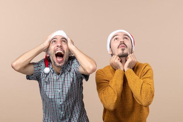 Vista frontale due ragazzi spaventati con cappelli di babbo natale uno mettendo le mani sulla sua testa l'altro sulla sua mascella in piedi su sfondo beige isolato Foto Gratuite