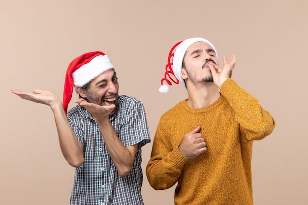 正面図サンタの帽子をかぶった2人の笑顔の男が、ベージュの孤立した背景にシェフのキスをしている 無料写真