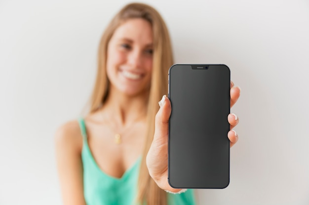 Front view unfocused woman showing her smartphone with empty screen Free Photo