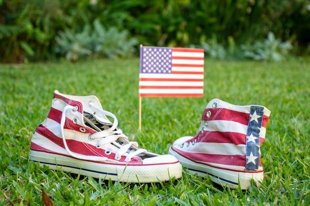 Bandiera e scarpe da tennis degli sua di vista frontale su erba Foto Gratuite