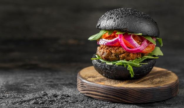 まな板に黒いパンが付いている正面図のベジーバーガー 無料写真