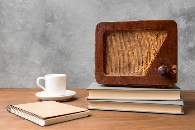 Radio d'epoca vista frontale su una pila di libri e caffè Foto Gratuite
