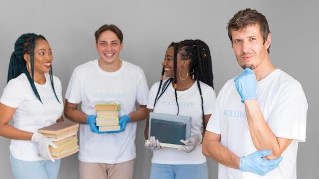 Organizzazione di volontariato di vista frontale che tiene libri per donazioni Foto Gratuite