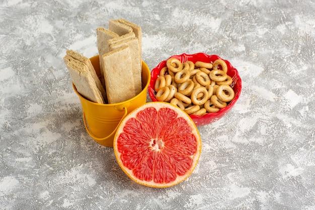 Vista frontale cialde e cracker con pompelmo su superficie bianca Foto Gratuite