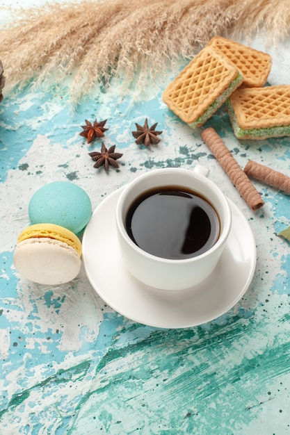 Front view waffles and macarons with cup of tea on blue surface cake biscuit sugar sweet cookie Free Photo