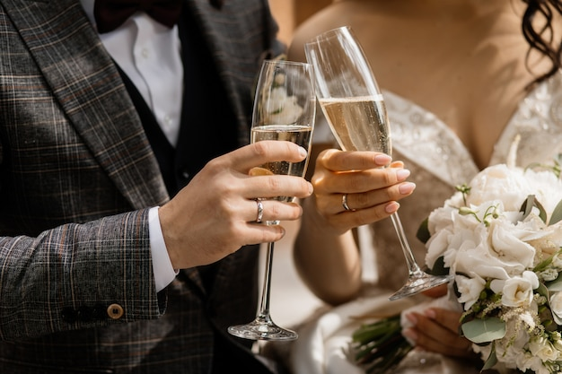 Front view of wedding couple's hands with champagne glasses and wedding bouquet Free Photo