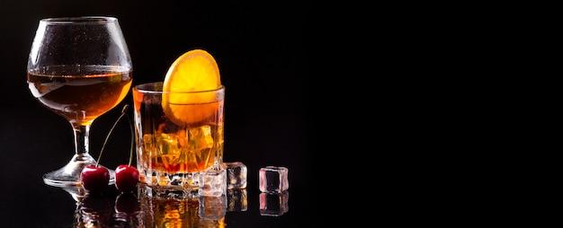 Виски, вид спереди с апельсином и бокалом для коньяка с копией пространства Бесплатные Фотографии