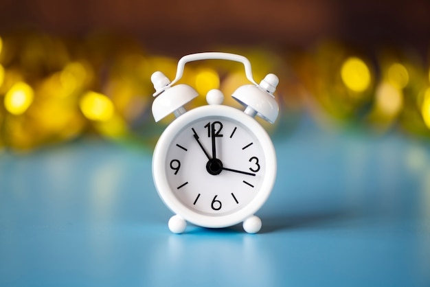 Front view white clock on blurred golden background Free Photo