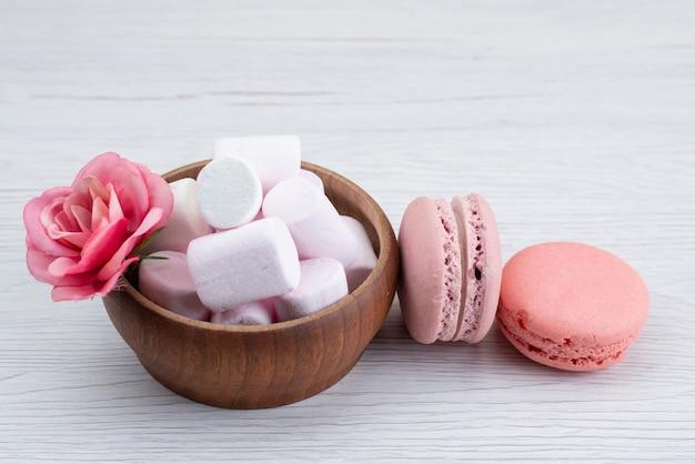 Un marshmallow bianco vista frontale con macarons francesi rosa sullo scrittorio bianco, colore dolce della caramella di zucchero Foto Gratuite