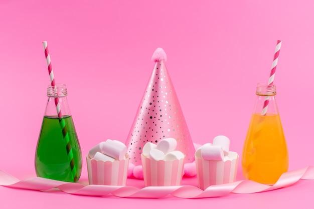 Un marshmallow bianco vista frontale insieme a bevande e berretto di compleanno sulla scrivania rosa, celebrazione della festa di compleanno Foto Gratuite