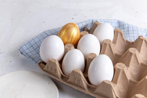 正面図白い背景に金色のものと白い全卵。 無料写真