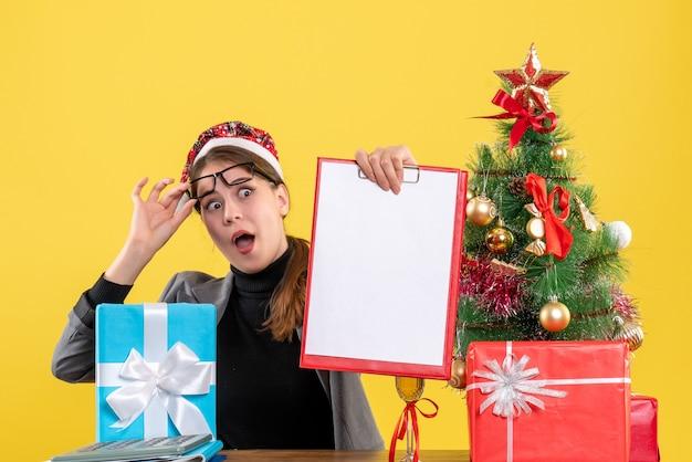 彼女の眼鏡を脱いでテーブルに座っているクリスマスの帽子をかぶった正面図の目を丸くした女の子クリスマスツリーとギフトカクテル 無料写真