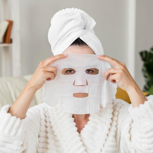 Вид спереди женщина, применяющая маску для лица Бесплатные Фотографии