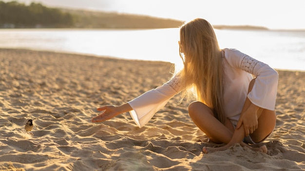 Front view of woman on the beach with bird Free Photo