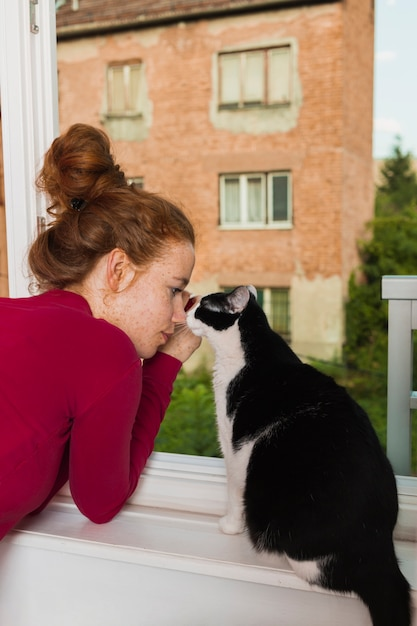 Front view woman and cat on balcony Free Photo
