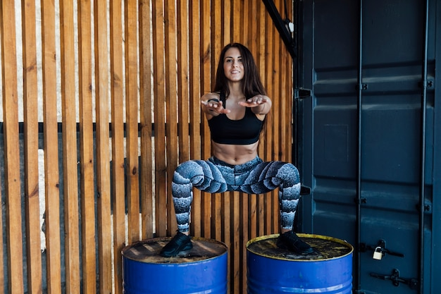 Front view of woman crouching on barrels Free Photo