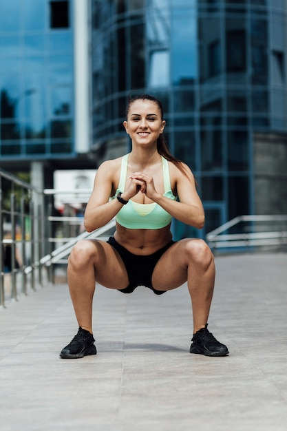 Front view of woman doing crouches Free Photo