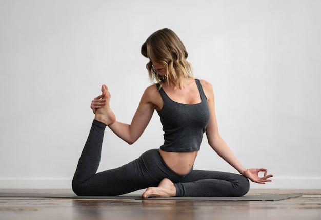 Vista frontale della donna che fa yoga a casa sulla stuoia Foto Gratuite