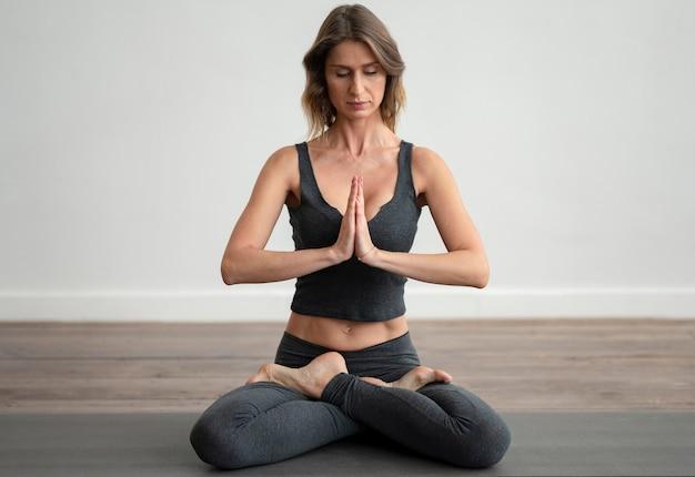 Vista frontale della donna che fa yoga sulla stuoia Foto Gratuite