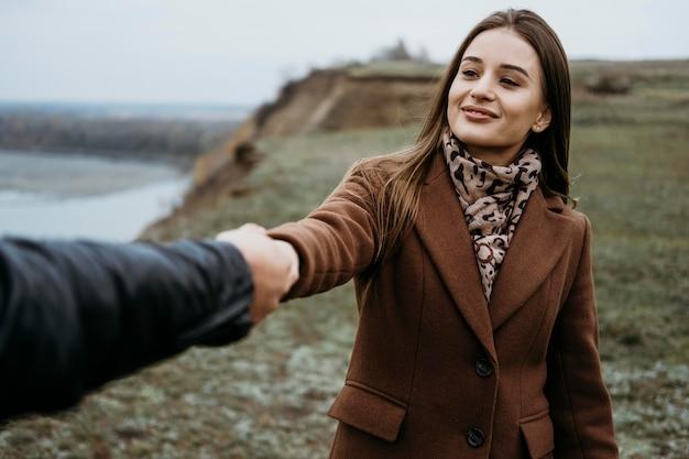 Vista frontale della donna che trascina il suo fidanzato lungo all'aperto Foto Gratuite