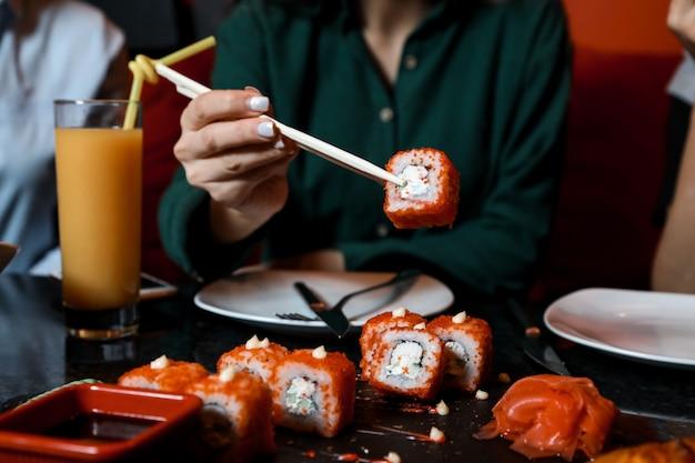 Donna di vista frontale che mangia sushi california rotoli con succo sul tavolo Foto Gratuite