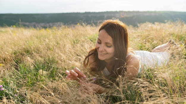 Front view of woman enjoying the grass in nature Free Photo