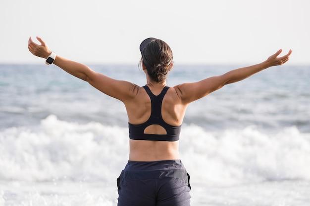 Вид спереди женщина, наслаждающаяся морем после бега Бесплатные Фотографии